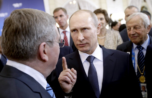 Russian President Vladimir Putin talks with International Olympic Committee President Thomas Bach at a welcoming event ahead of the 2014 Winter Olympics (Photo Credit: David Goldman-Pool/Getty Images).