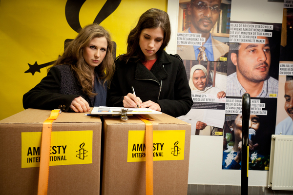 Nadya and Masha sign a petition calling for the Russian government to stop their crackdown on freedom of expression (Photo Credit: Jorn van Eck / Amnesty International).