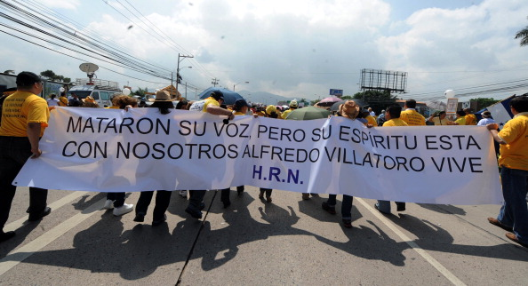 Journalists, journalism students and relatives of slain journalists take part in a demonstration during the celebration of the Day of the Journalist in Tegucigalpa, Honduras (Photo Credit: Orlando Sierra/AFP/Getty Images).