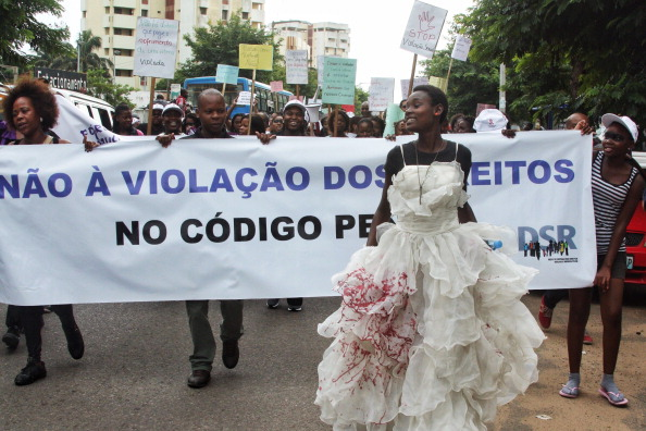 A woman wears a blood-stained wedding dress as she takes part in a protest against a law that allows convicted rapists to be freed from prosecution if they marry the victim (Photo Credit: Jinty Jackson/AFP/Getty Images).