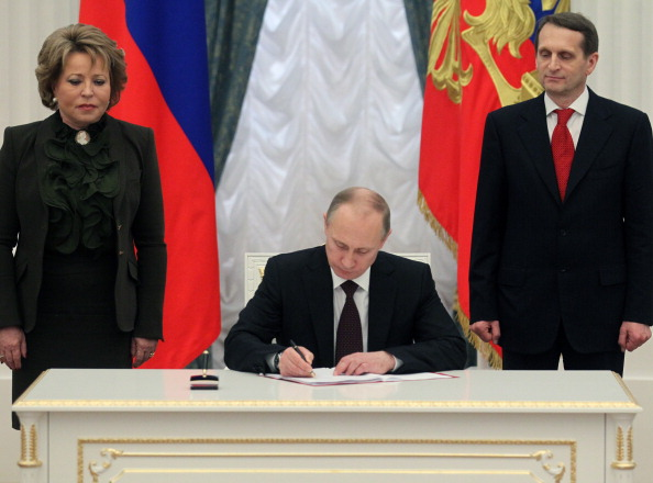 Russian President Vladimir Putin signing the final decree completing annexation of Crimea on March 21, 2014 in Moscow (Photo Credit: Sasha Mordovets/Getty Images).