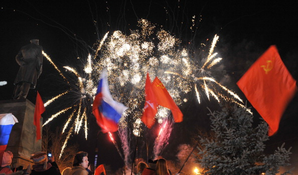 People wave Russian and Soviet flags as they look at fireworks in the center of the Crimean city of Sevastopol celebrating the annexation of the peninsula by Russia (Photo Credit: Viktor Drachev/AFP/Getty Images).