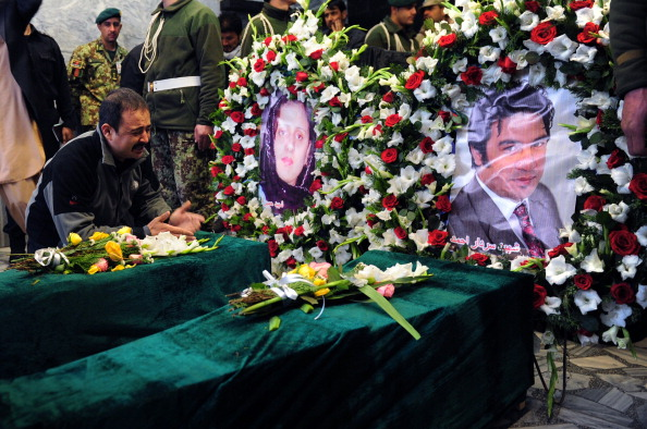 The nephew of slain Afghan AFP reporter Sardar Ahmad laments over the coffins of two of Sardar's children alongside images of Sardar's wife and Sardar during funeral ceremonies on March 23, 2014 (Photo Credit: Roberto Schmidt/AFP/Getty Images).