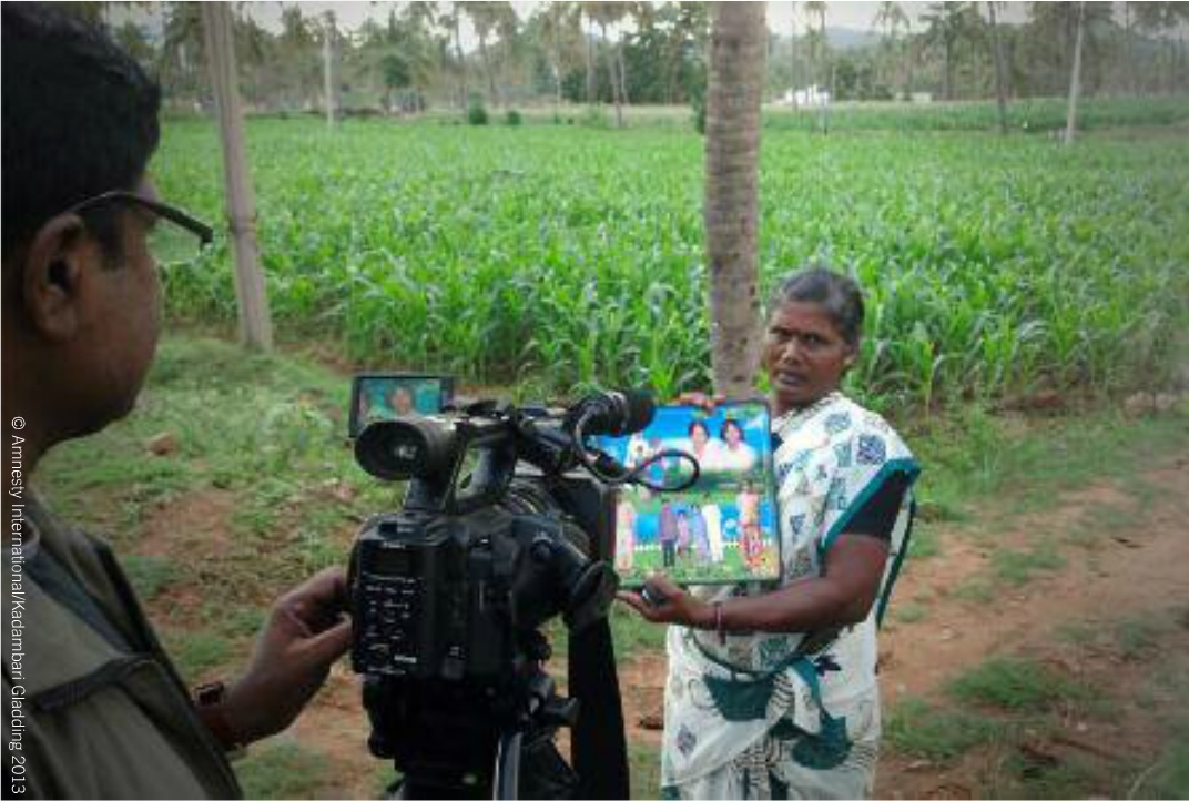 Jayamary, Simon's younger sister, holds a family photo from 30 years ago during the filming of a video by Amnesty International India (Photo Credit: Amnesty International).