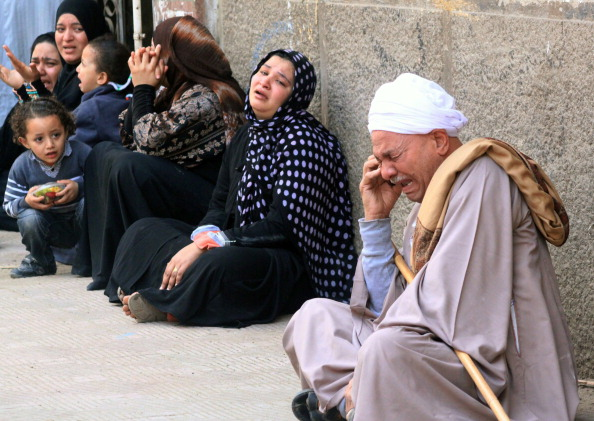 Egyptian relatives of supporters of ousted Islamist president Mohamed Morsi cry sitting outside the courthouse after the court ordered the execution of hundreds of Morsi supporters after only two hearings in March (Photo Credit: AFP/Getty Images).