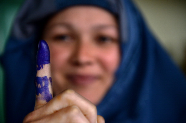 An Afghan voter shows her inked finger after she cast her ballot at a local polling station (Photo Credit: Shah Marai/AFP/Getty Images).