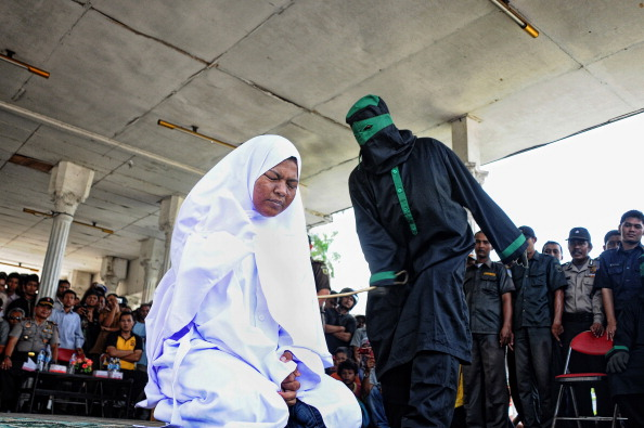 A crowd watches as a woman is caned by a sharia police officer dressed in black robes at a public square in Aceh, Indonesia's only province that practices partial sharia law (Photo Credit: Riza Lazuardi/AFP/Getty Images).