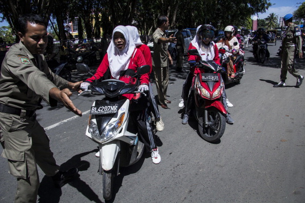 Aceh's Shari'a laws targeting women have made news a number of times, including this spring when police pulled women over and forcing them to sit sideways on motorbikes, with their legs dangling by the rear wheel (Photo credit should read REZA JUANDA/AFP/Getty Images).