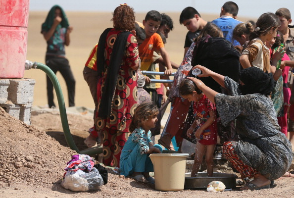Iraqi displaced people cool down at a temporary camp set up to shelter Iraqis fleeing violence in northern Iraq on June 18 (Photo Credit: Karim Sahib/AFP/Getty Images).