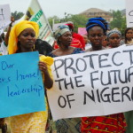 Women hold banners during a march of Nigeria women and mothers of the kidnapped girls of Chibok, calling for their freedom (Photo Credit: Philip Ojisua/AFP/Getty Images).