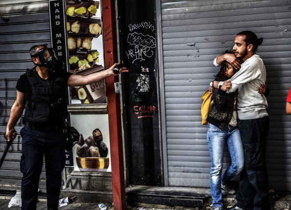 A man protects a woman as they face a police officer dispersing protesters who gathered near Taksim square in Istanbul as the police blocked access to the square during the one year anniversary of the Gezi park and Taksim square demonstrations (Photo Credit: Bulent Kilic/AFP/Getty Images).