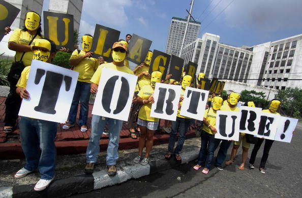 Activists in masks at an Amnesty International rally in Manila calling for an end to torture and human rights violations in the Philippines (Photo Credit: Jes Aznar/AFP/Getty Images).