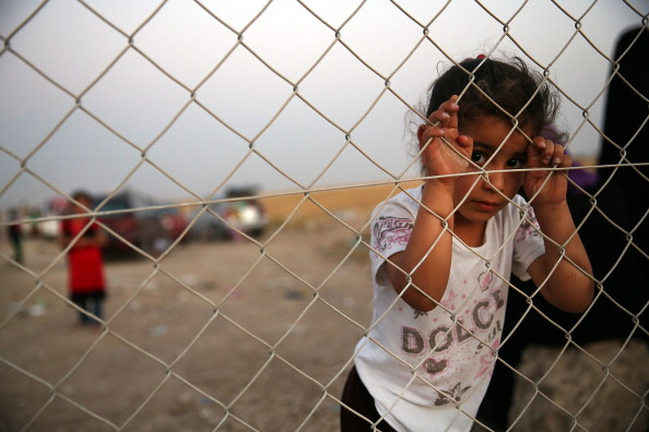 An Iraqi child waits with her family outside of a temporary displacement camp for Iraqis caught-up in the fighting in Khazair, Iraq. Khazair is now home to an estimated 1,500 internally displaced persons (IDP's) with the number rising daily (Photo Credit: Spencer Platt/Getty Images).