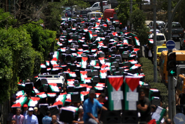 RAMALLAH, WEST BANK - JULY 23: People carry mock coffins covered with Palestinian flag are prepared for the killed people during the Israeli attacks to Gaza on July 23, 2014, in Ramallah, West Bank. . (Photo Credit: Shadi Hatem/Anadolu Agency/Getty Images)
