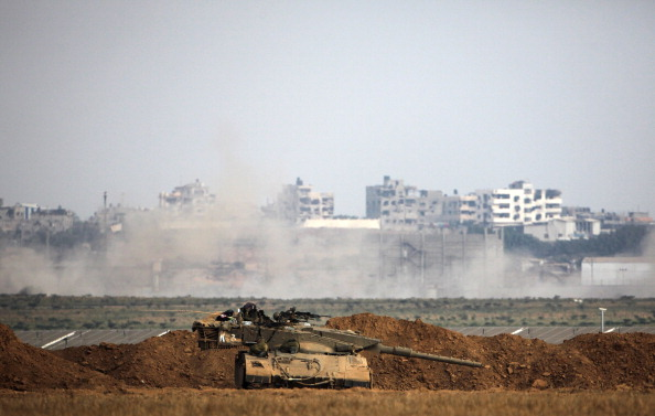 An Israeli army Merkava tank is positioned along the border in front of buildings in the Gaza Strip on July 28, 2014. (Photo credit: David Buimovitch/AFP/Getty Images)