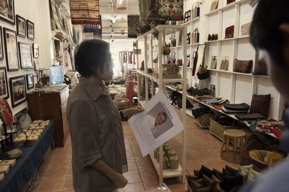 Sombath Somphone's wife, Ng Shui Meng, handles a 'missing person' poster of her husband at Saoban, a store selling Lao Village handicrafts that she established with her husband. (Photo credit: Gilles Sabrie/LightRocket via Getty Images)