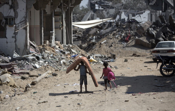 Palestinians salvage items from the rubble of destroyed buildings in part of Gaza City's al-Tufah neighbourhood as the fragile ceasefire in the Gaza Strip entered a second day on August 6, 2014. (Photo credit: MAHMUD HAMS/AFP/Getty Images)