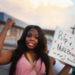 Arniesha Randall protests the killing of 18-year-old Michael Brown who was shot by police in Ferguson, Missouri. Police responded with tear gas and rubber bullets as residents and their supporters protested the shooting by police of an unarmed black teenager named Michael Brown (Photo Credit: Scott Olson/Getty Images).