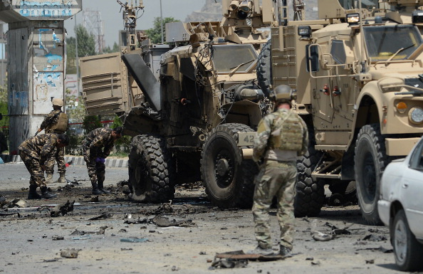 U.S. soldiers part of NATO-led International Security Assistance force (ISAF) and Afghan security forces inspect the wreckage of an armored vehicle at the site of a suicide attack in Kabul on August 10, 2014. Photo credit: Shah Marai/AFP/Getty Images)