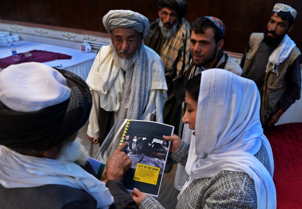 Afghan relatives of civilian victims of the country's conflict examine the Amnesty International report detailing those killed by U.S. forces in the country at a press conference in Kabul on August 11, 2014. The families of thousands of civilians killed by American forces in Afghanistan have been left without justice or compensation. (Photo credit: Wakil Kohsar/AFP/Getty Images)