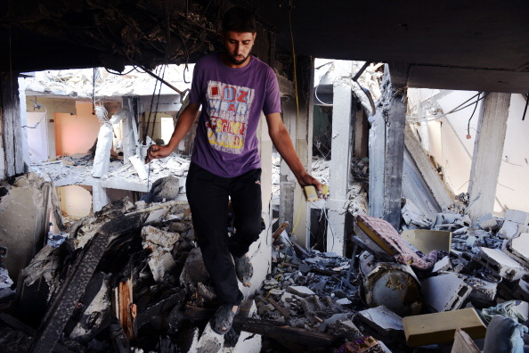 Ziad Assam walks on rubble inside an apartment complex where he used to live on August 13, 2014. It was heavily damaged in fighting between Israel and Hamas during four weeks of fighting in northern Gaza strip. (Photo credit: Roberto Schmidt/AFP/Getty Images)