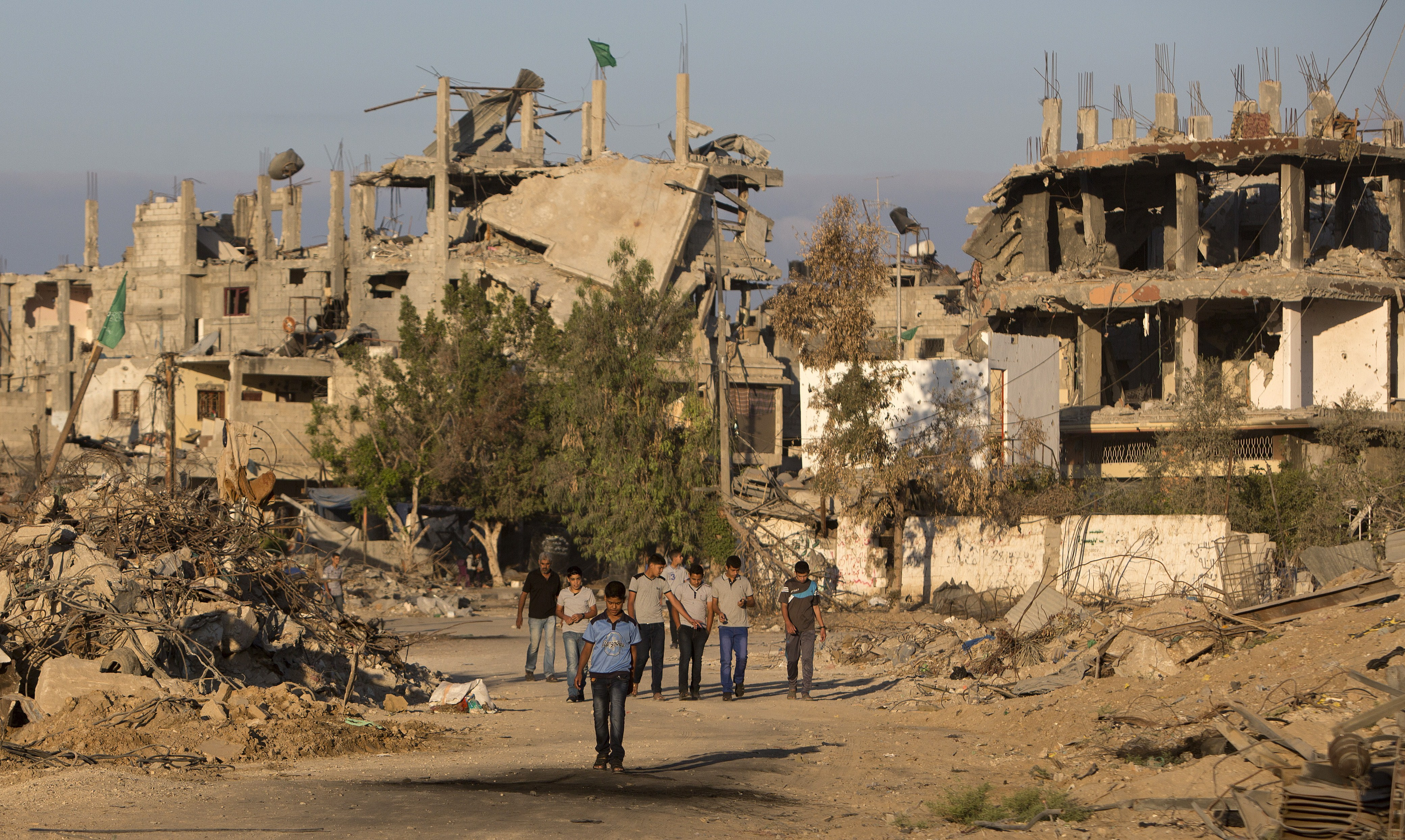 Palestinian boys walk past buildings which were destroyed by Israeli strikes on their way to school in the Shejaiya neighbourhood of Gaza City on September 14, 2014 on the first day of the new school year. (MAHMUD HAMS/AFP/Getty Images)