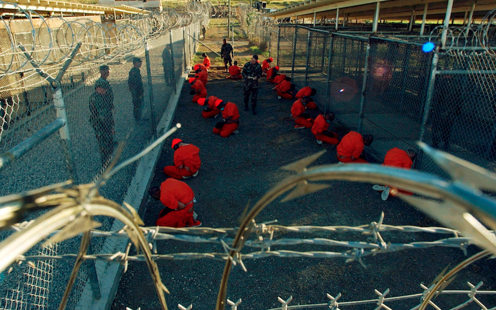 Detainees in orange jumpsuits sit in a holding area under the watchful eyes of Military Police at Camp X-Ray at Naval Base Guantanamo Bay, Cuba, during in-processing to the temporary detention facility on January 11, 2002. REUTERS/DoD/Shane T. McCoy