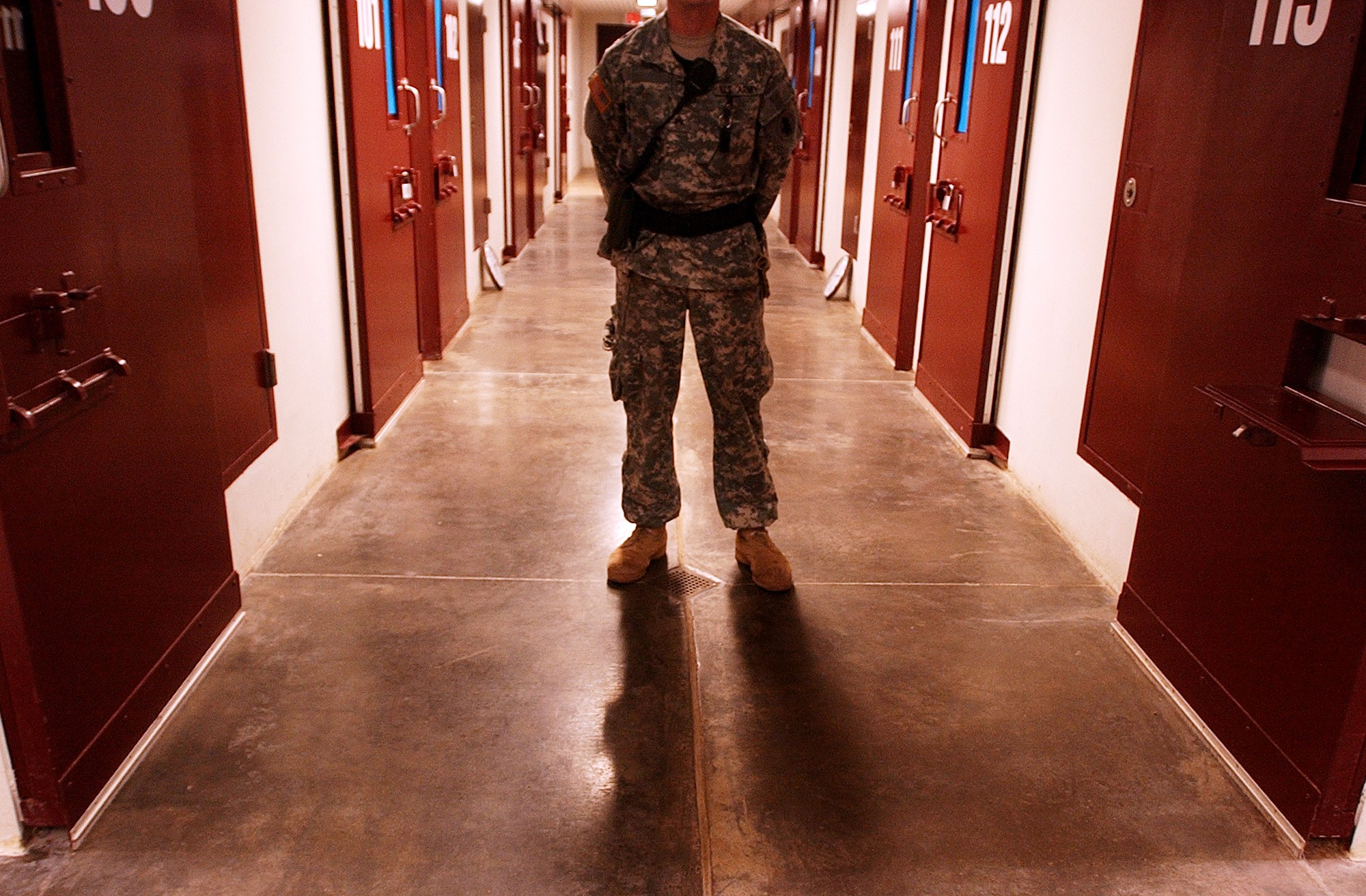 US Army Soldiers stand guard on a cell block inside Camp Five at the detention centre, Guantanamo Bay, Cuba, 14 November 2006. Camp Five is one of six camps that comprise the detention center and has been built with many features that can be found in many maximum-security prisons in the United States.