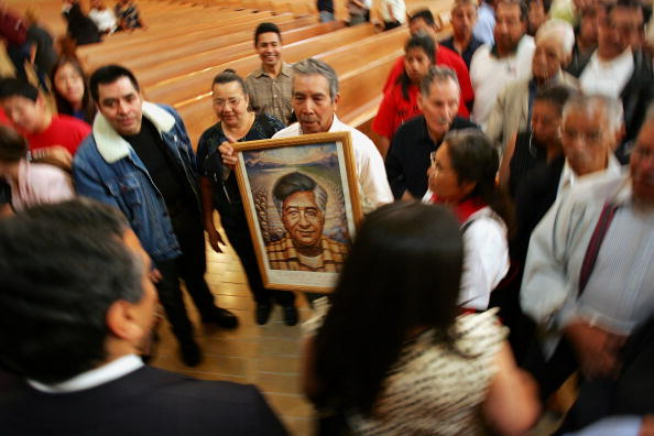 A man holds a portrait of Cesar Chavez at a mass in Los Angeles. Chavez was born on March 31, 1927. (c) David McNew/Getty Images)