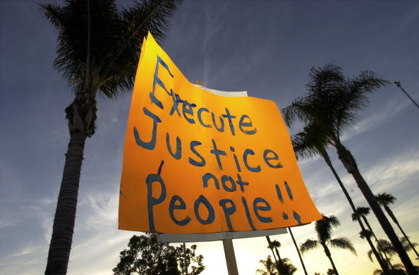 390763 02: A protester holds a sign up against a backdrop of palm trees during an anti-death penalty protest on the eve of the second federal execution in nearly four decades June 18,2001 in Santa Ana, CA. Juan Garza, who was sentenced to death by a judge who believes that the death penalty is morally wrong, is scheduled to die a week after the killing of Oklahoma bomber Timothy McVeigh in Terra Haut, ID. (Photo by David McNew/Getty Images)