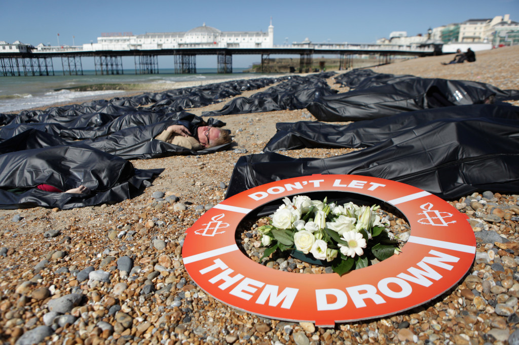SOS Europe - Die-in, Brighton Beach, England. Photo shows people lying on Brighton beach ( Brighton Pier in the background ) in black body bags. A life saving ring on the pebbles reads ' Don't Let Them Drown.  Brighton beach was covered in 200 body bags as Amnesty International volunteers raised awareness of the plight of thousands of migrants ahead of emergency EU talks on 23rd April 2015. Local Amnesty members and volunteers zipped themselves into some of the body bags at around 10am, alongside a banner saying #DontLetThemDrown. Campaigners hope the protest, organised ahead of an EU meeting on the mounting death toll in the Mediterranean seas, will highlight the UK?s ?shameful? response to the crisis.