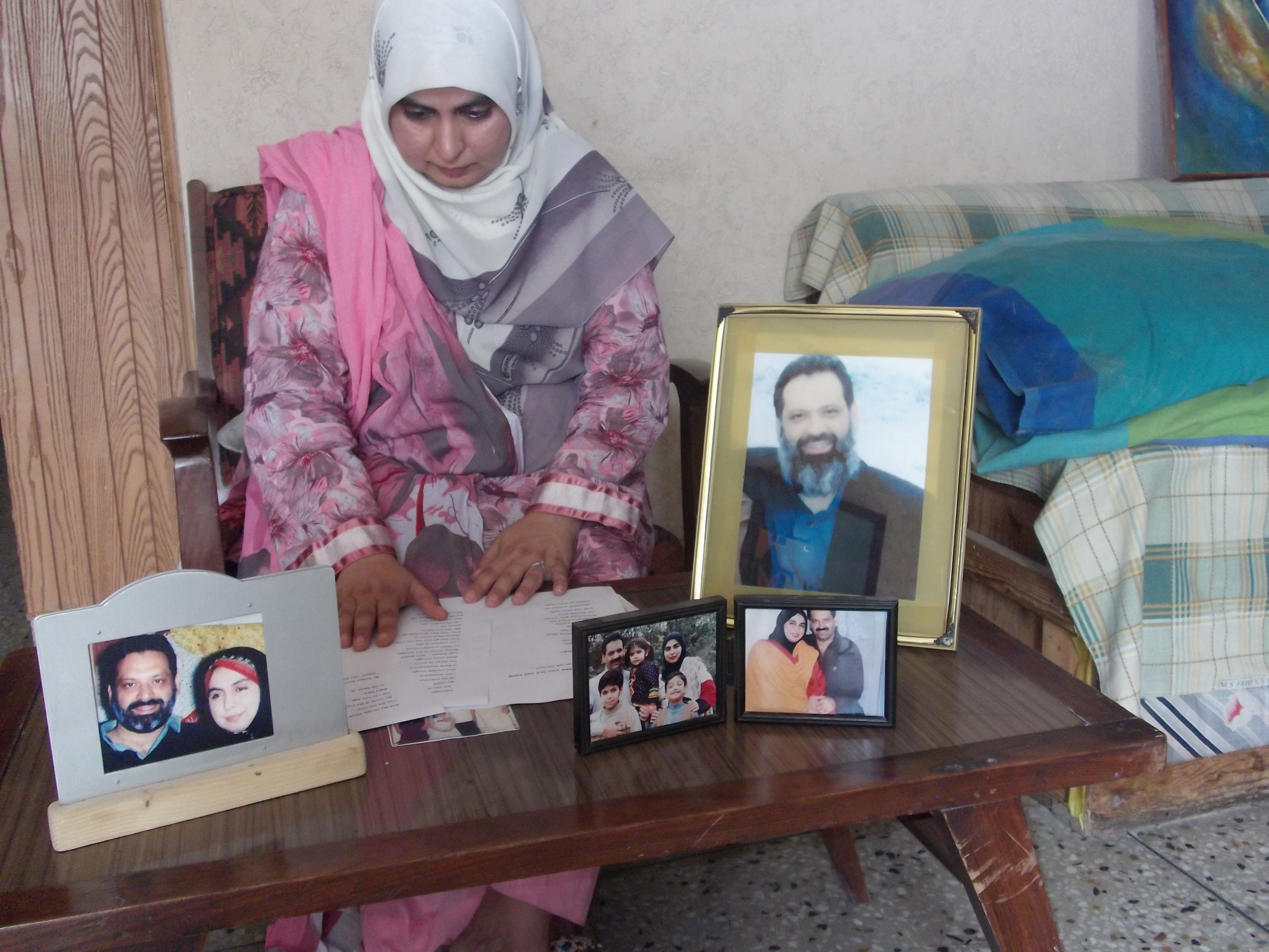 Amina Masood Janjua with photos of her husband, Masood Ahemd Janjua, a businessman from Rawalpindi.  Masood Janjua, along with his friend Faisal Faraz, an engineer from Lahore, were  forcibly disappeared? on 30 July 2005, at some point during a two-hour bus journey from Rawalpindi to Peshawar.  Their fate and whereabouts remain unknown.