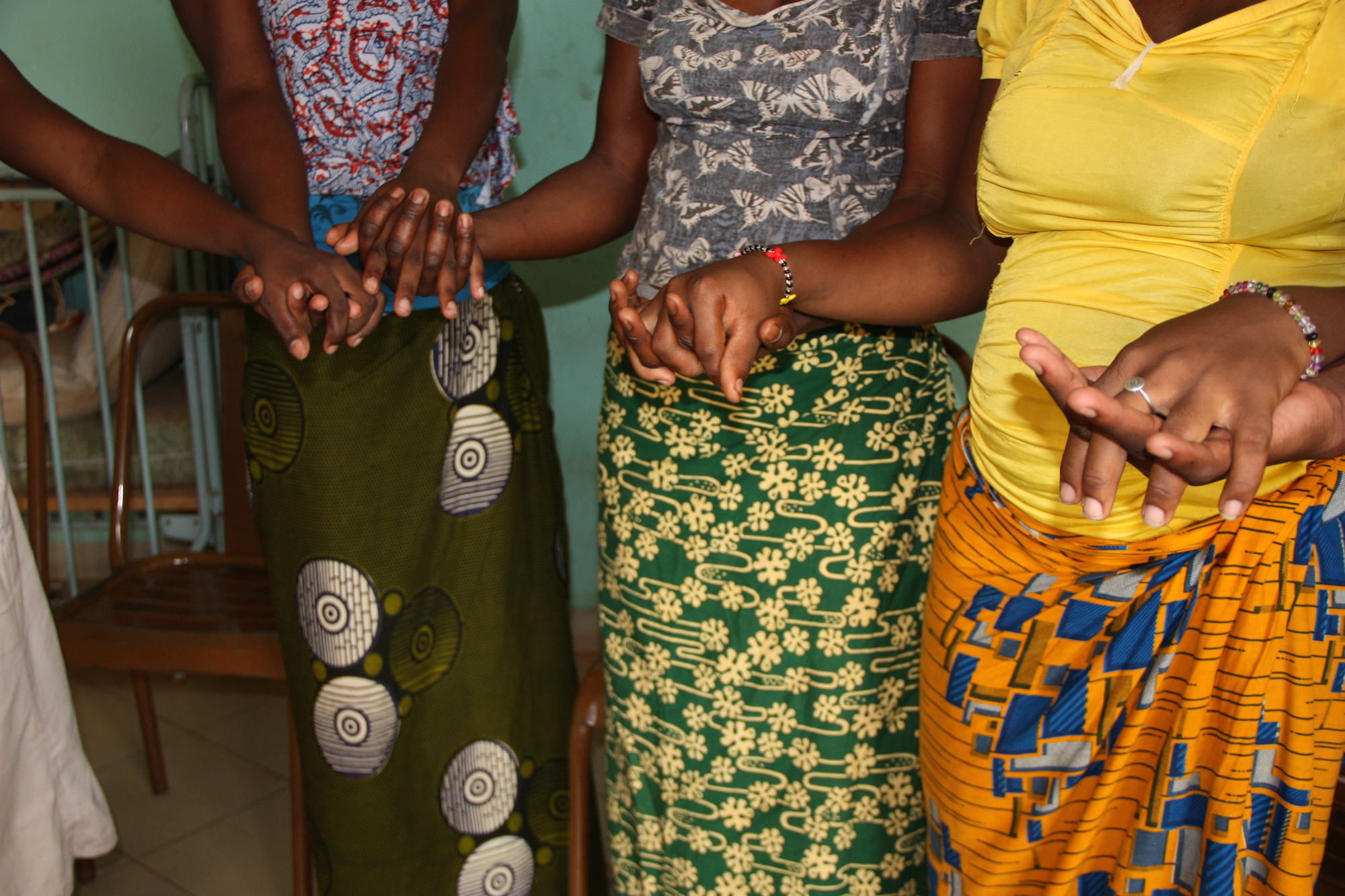 Young women hold hands in a shelter run by Nuns, these young women have courageously fled forced marriage or early and unwanted pregnancies. Ouagadougou. July 2014
