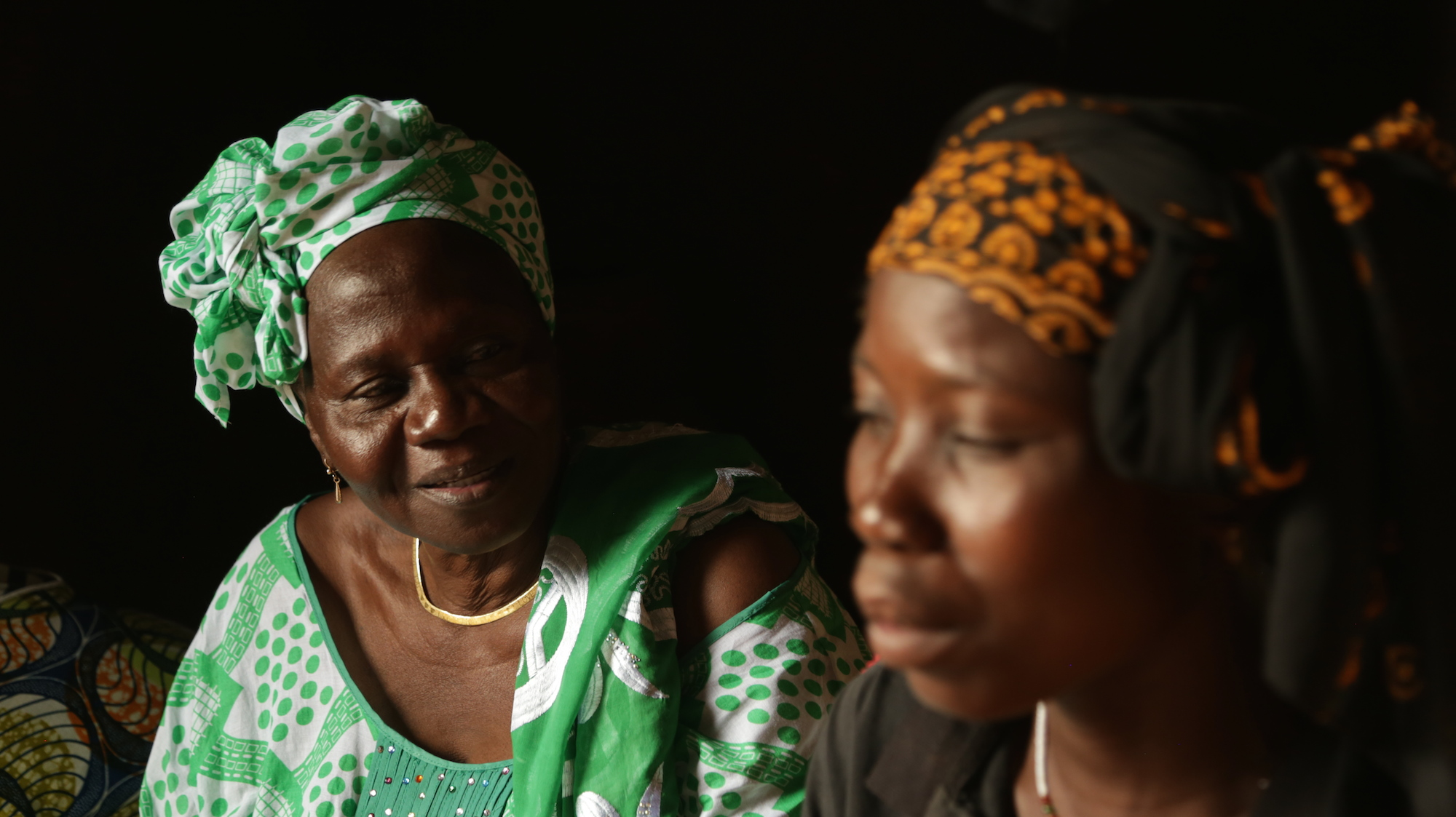Women's rights activist Bibata Ouedraogo exchanges with Abibou Sanga during a session on sexual and reproductive rights in the village of Sissaba, Burkina Faso.