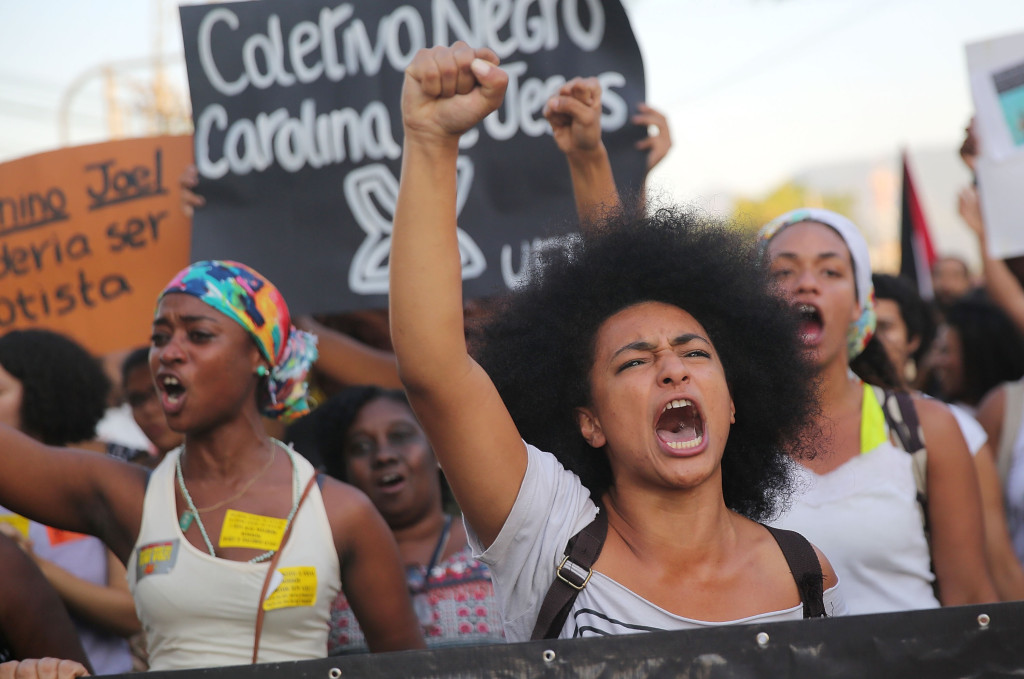 Demonstrators march through the Manguinhos favela to protest against police killings of blacks on August 22, 2014 in Rio de Janeiro, Brazil. Every year, Brazil's police are responsible for around 2,000 deaths, one of the highest rates in the world. Many of the deaths in Rio involve blacks killed in favelas, also known as slums. (Photo by Mario Tama/Getty Images)