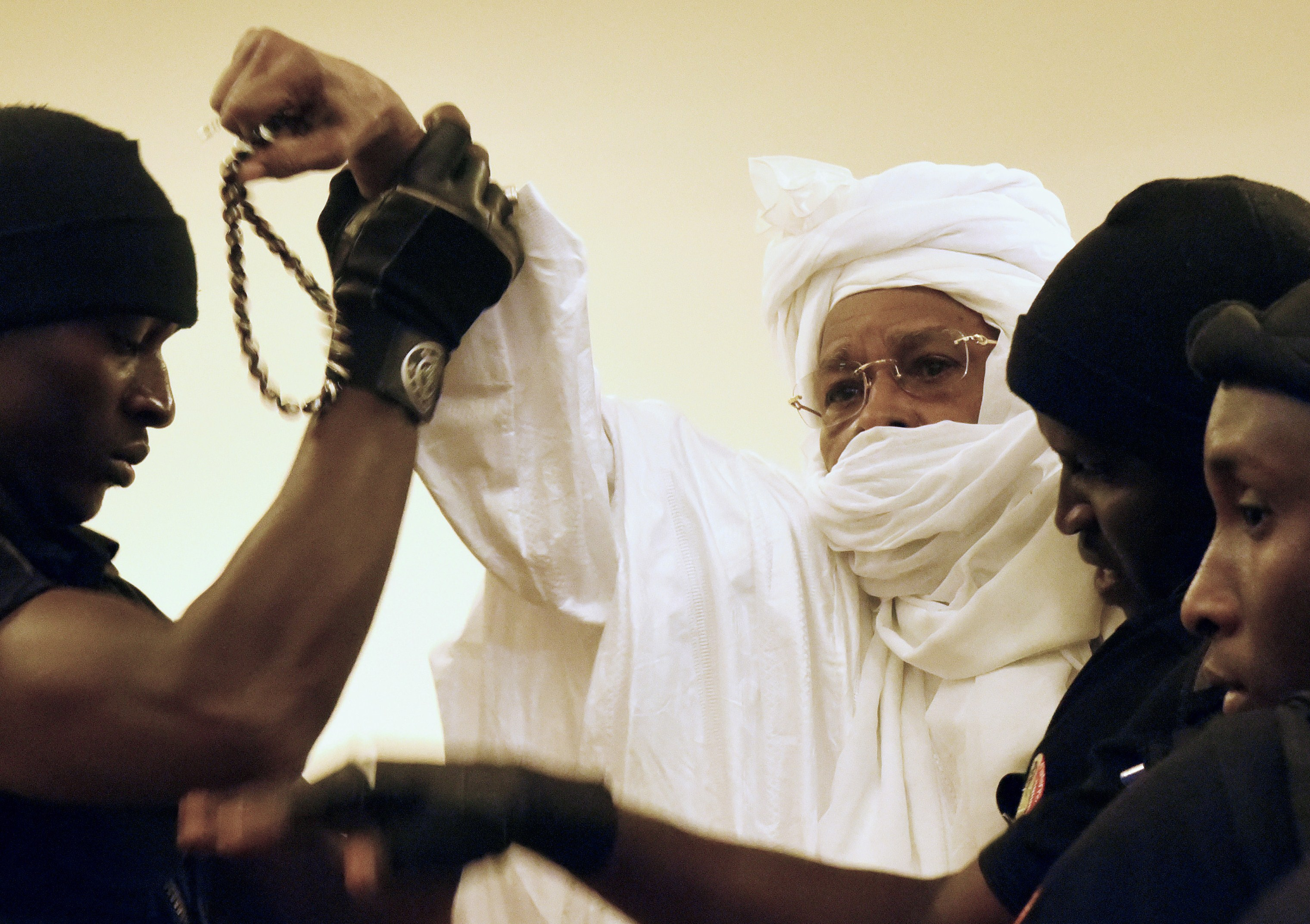 Former Chadian dictator Hissene Habre is escorted by prison guards into the courtroom for the first proceedings of his trial by the Extraordinary African Chambers in Dakar on July 20, 2015. (SEYLLOU/AFP/Getty Images)