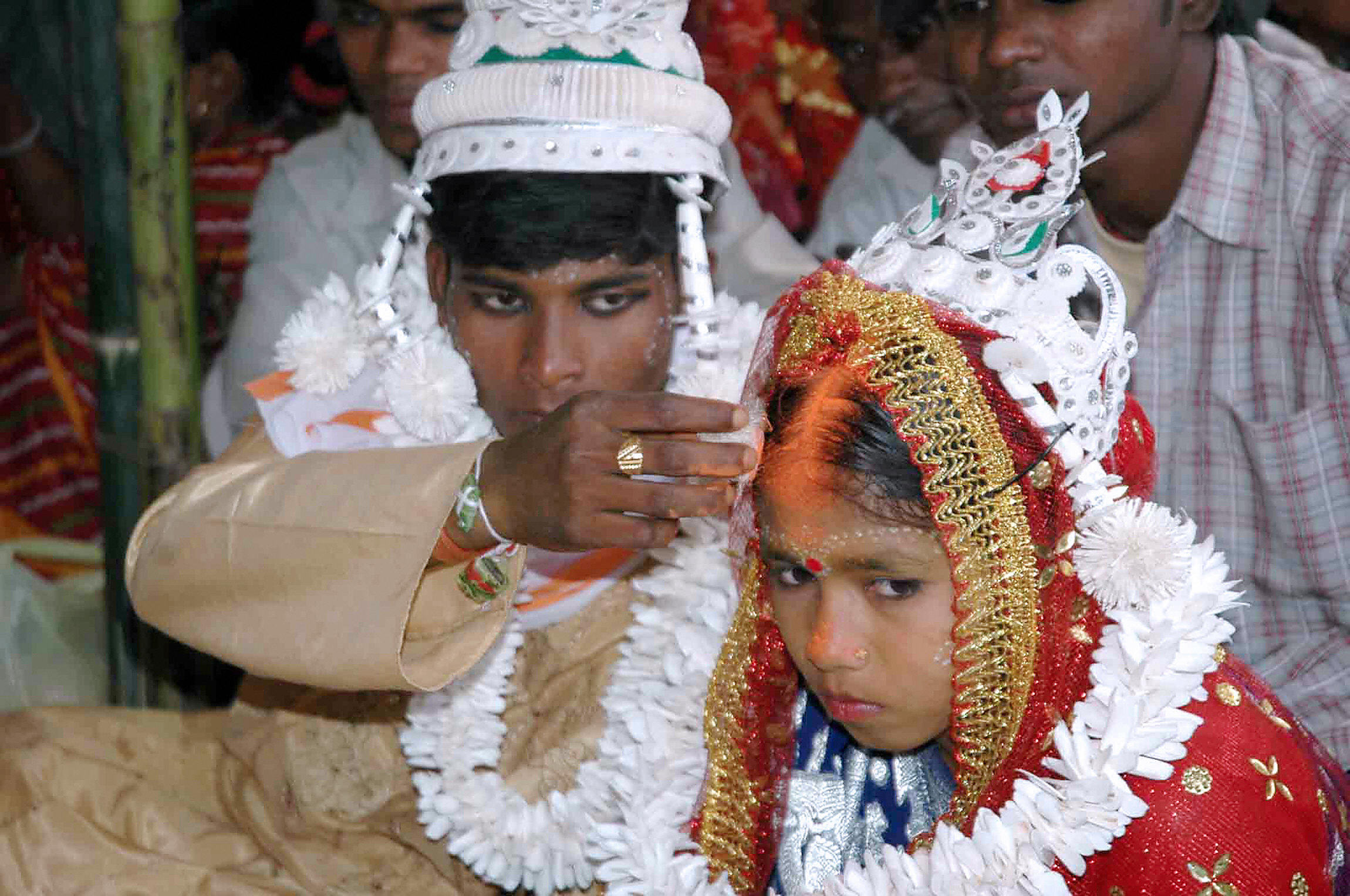 Indian groom puts vermilion on the forehead of his underage bride during a mass marriage in Malda, India 02 March 2006. (STRDEL/AFP/Getty Images)