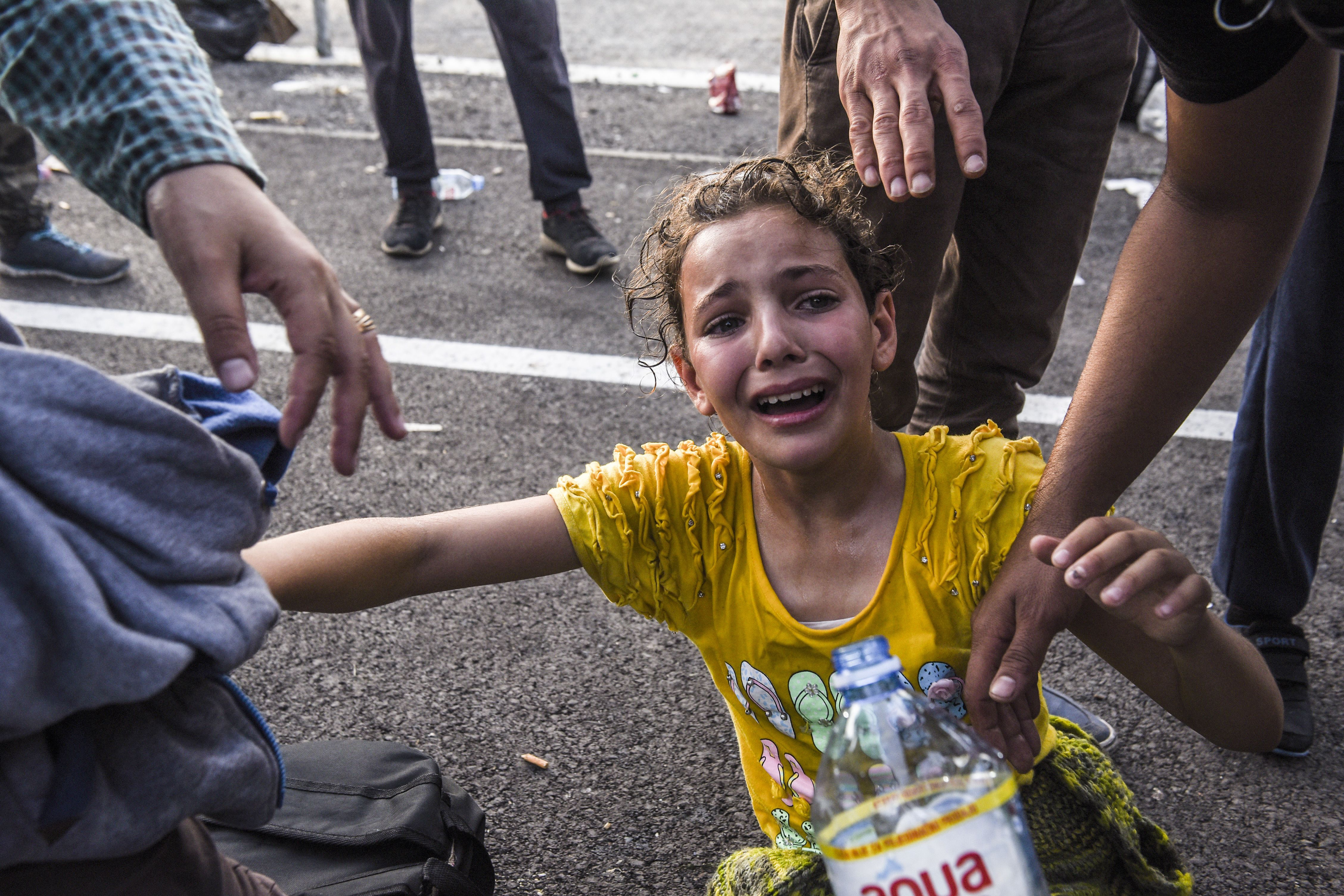 A girl reacts after receiving tear gas at the Hungarian border with Serbia. ARMEND NIMANI/AFP/Getty Images