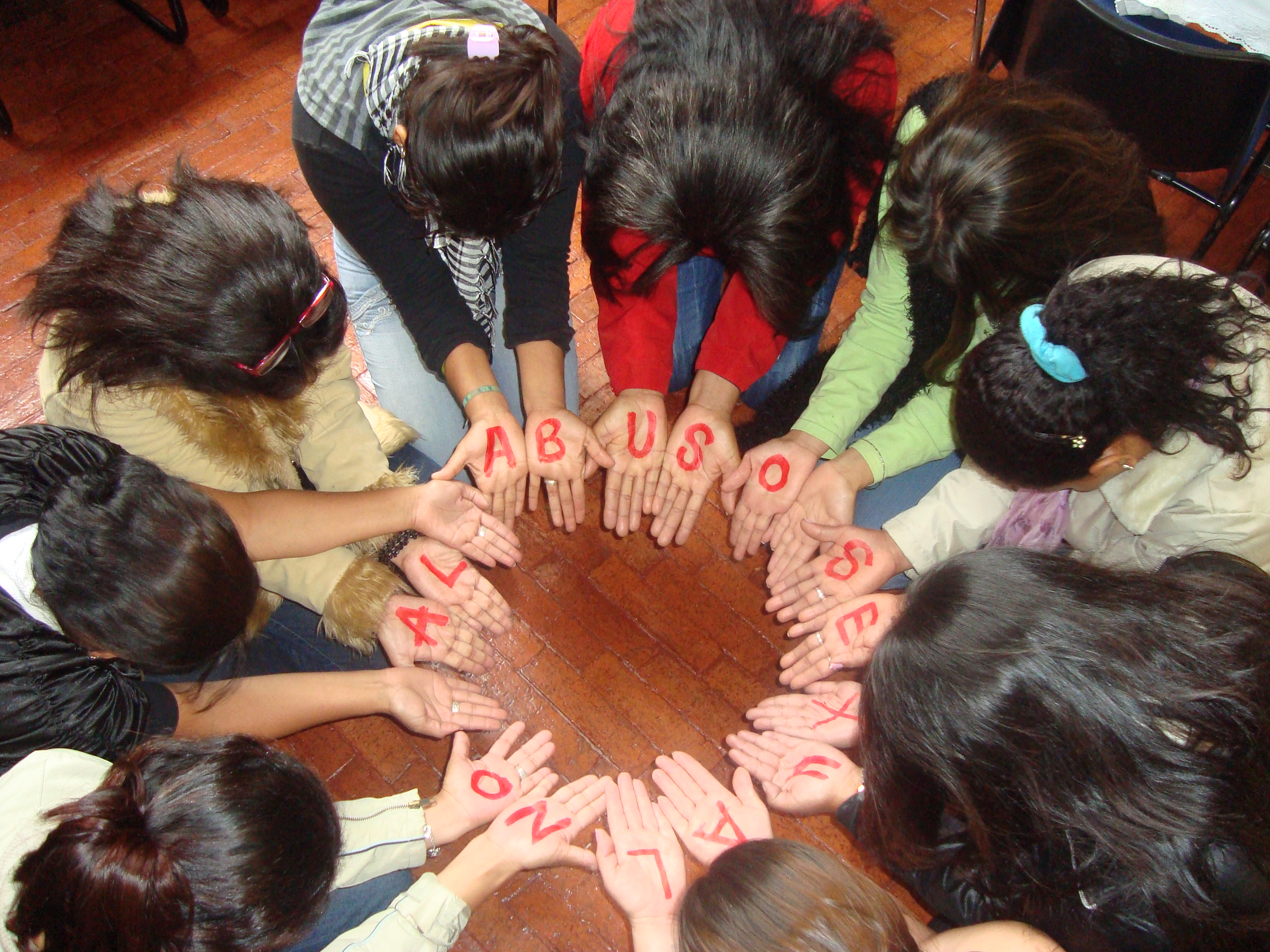"Members of a support group for survivors of sexual violence create a circle with their hands, Bogotá, Colombia, March 2011. The letters on the hands of the women in a circle form the words ""No al abuso sexual"" (No to sexual abuse). They are a group of women who have been victims of sexual violence in the armed conflict in Colombia who meet regularly."