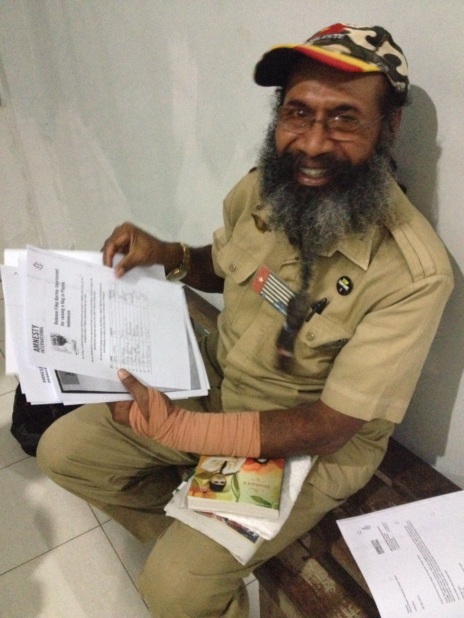 Filep Karma with petitions signed by Amnesty International activists calling for his release. He is smiling. Filep Karma is serving 15 years in prison for raising a flag. A prominent advocate for the rights of Indonesia's Papuan population, Filep Karma was arrested for taking part in a peaceful ceremony on December 1, 2004, which included the raising of the Morning Star flag, a Papuan symbol. Amnesty International considers Filep Karma to be a prisoner of conscience who has been imprisoned solely for the peaceful and legitimate exercise of his right to freedom of expression.