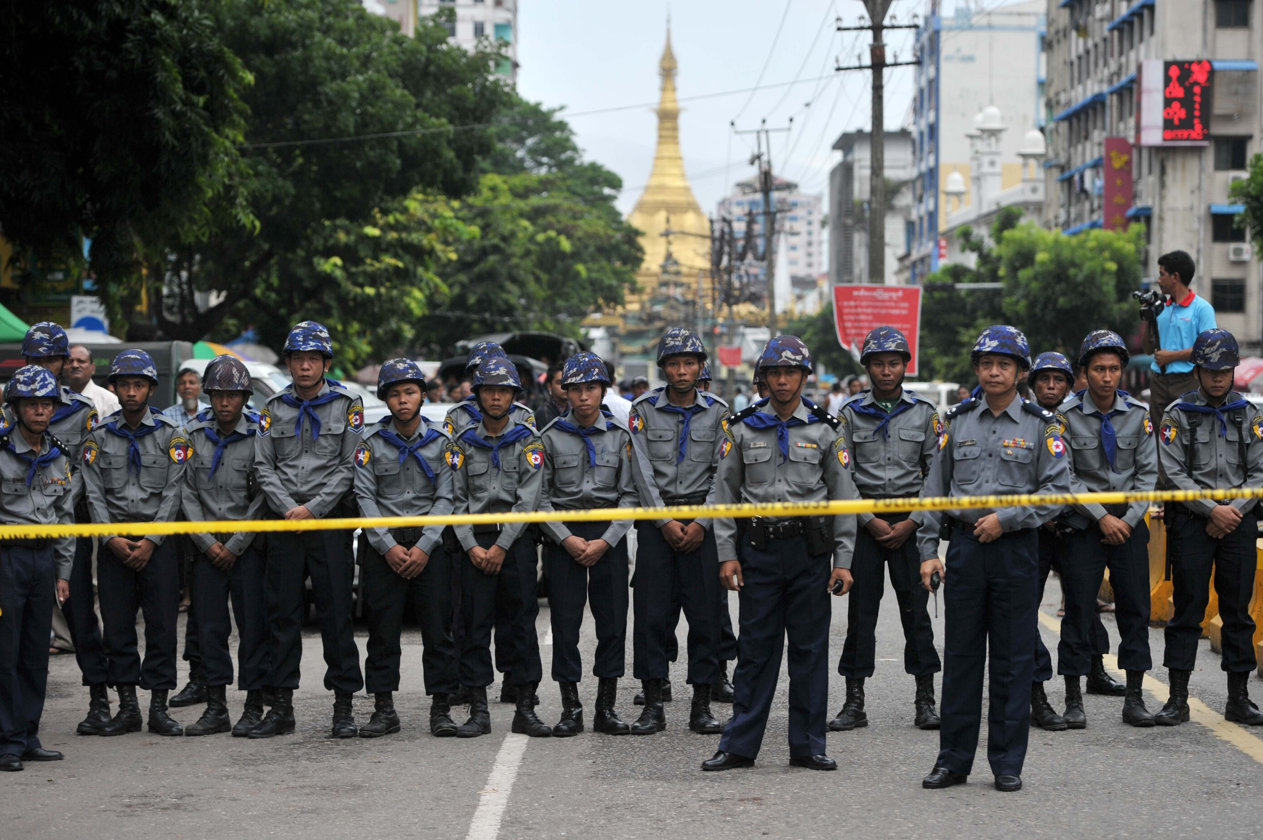 Police hold positions as they face off against student protesters during a demonstration against unelected soldiers who make up a quarter of parliamentary seats, in Yangon on June 30, 2015. Angry crowds scuffled with hundreds of police in downtown Yangon June 30 in a protest against the Myanmar army's veto on constitutional change, blamed for the defeat last week of a charter reform bill backed by Aung San Suu Kyi. (YE AUNG THU/AFP/Getty Images)