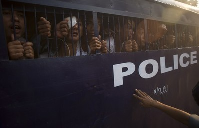 Student protesters try to speak to their family members from a prison vehicle as they are transported to a court in Letpadan on March 11, 2015. Anxious families of scores of arrested Myanmar activists on March 11 sought news of relatives detained by police in a violent student protest crackdown, which sparked international condemnation and fears of a return to junta-era repression. AFP PHOTO / Ye Aung THU        (Photo credit should read Ye Aung Thu/AFP/Getty Images)