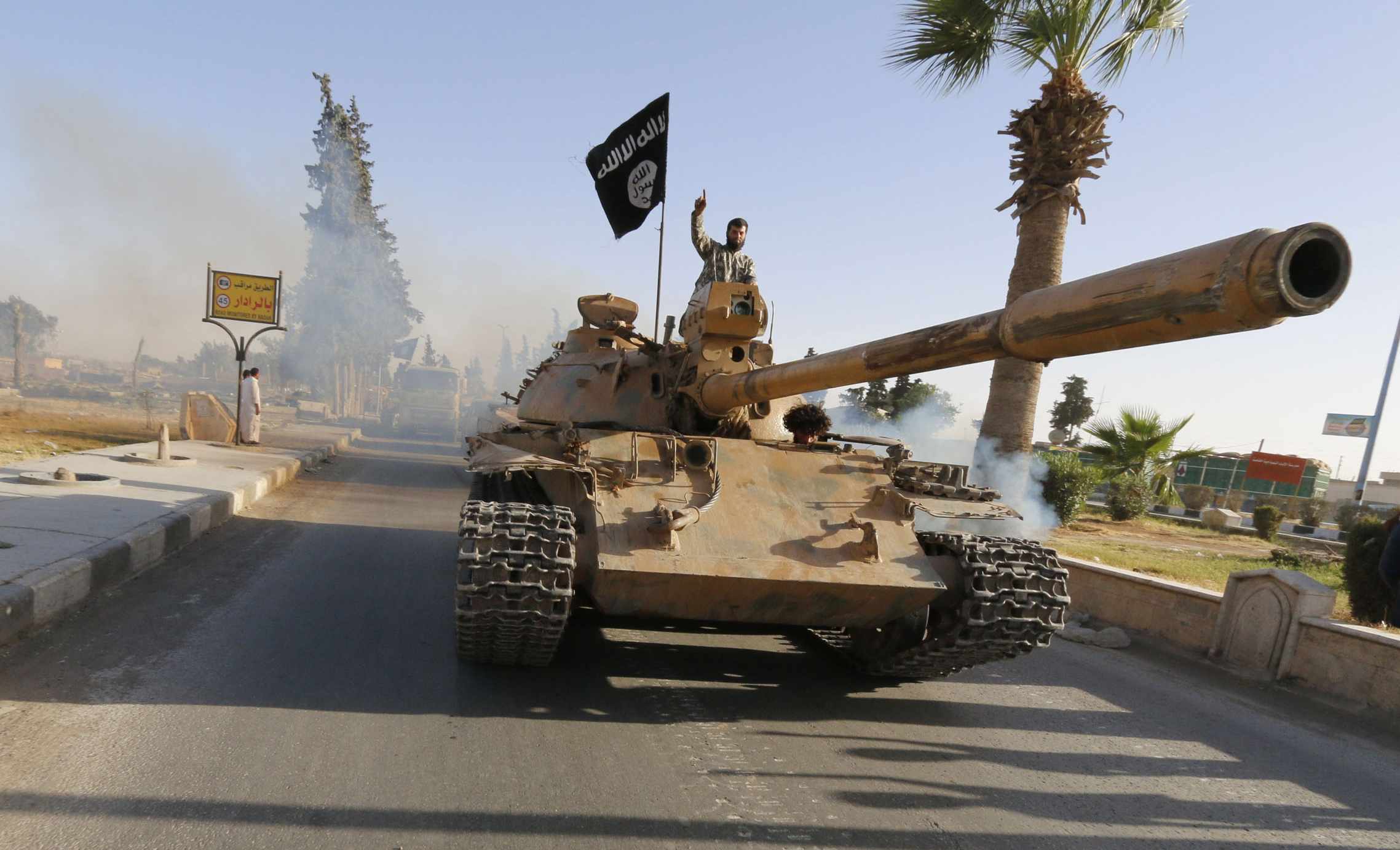 "Militant Islamist fighters on a tank take part in a military parade along the streets of northern Raqqa province June 30, 2014. Militant Islamist fighters held a parade in Syria's northern Raqqa province to celebrate their declaration of an Islamic ""caliphate"" after the group captured territory in neighbouring Iraq, a monitoring service said. The Islamic State, an al Qaeda offshoot previously known as Islamic State in Iraq and the Levant (ISIL), posted pictures online on Sunday of people waving black flags from cars and holding guns in the air, the SITE monitoring service said.  REUTERS/Stringer (SYRIA - Tags: POLITICS CIVIL UNREST CONFLICT)"