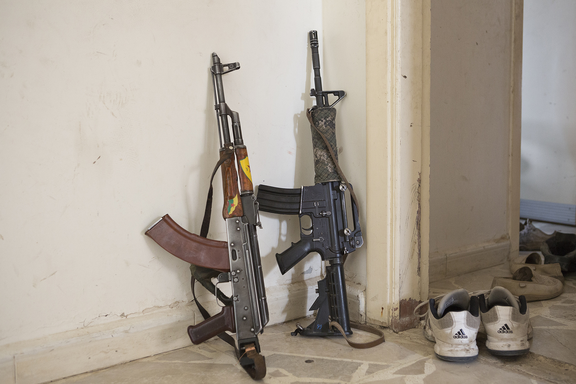 28/09/2014. Al-Yarubiyah, Syria. A Chinese made Kalashnikov and American M4 rifle (the latter captured from ISIS militants) lean against a wall in a building occupied by Syrian Kurdish YPG fighters in Al-Yarubiyah, Syria.