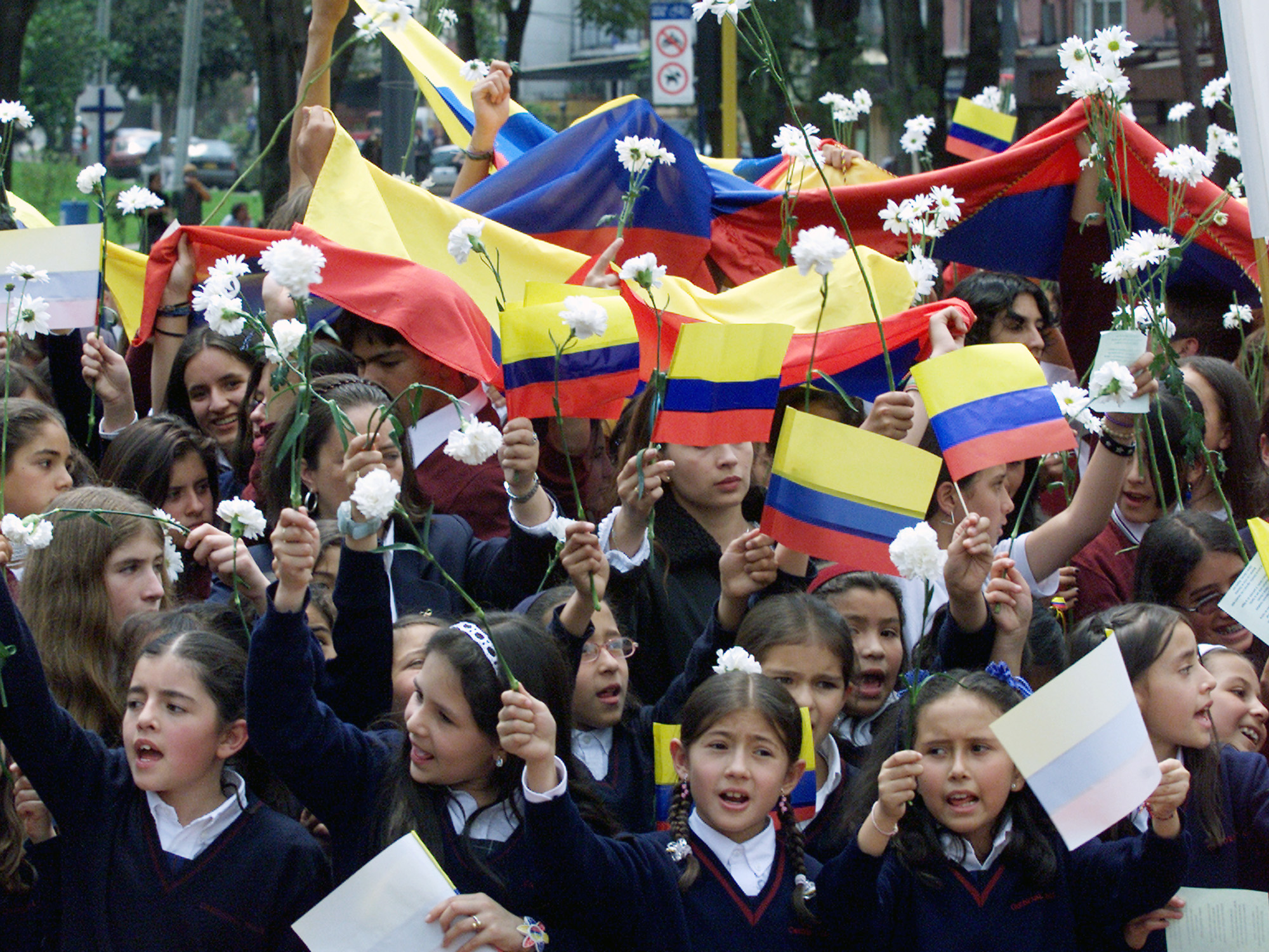 Students celebrating International Women's Day hold Colombian flags and flowers during march to demand the release of dozens of kidnapped children, Bogota.