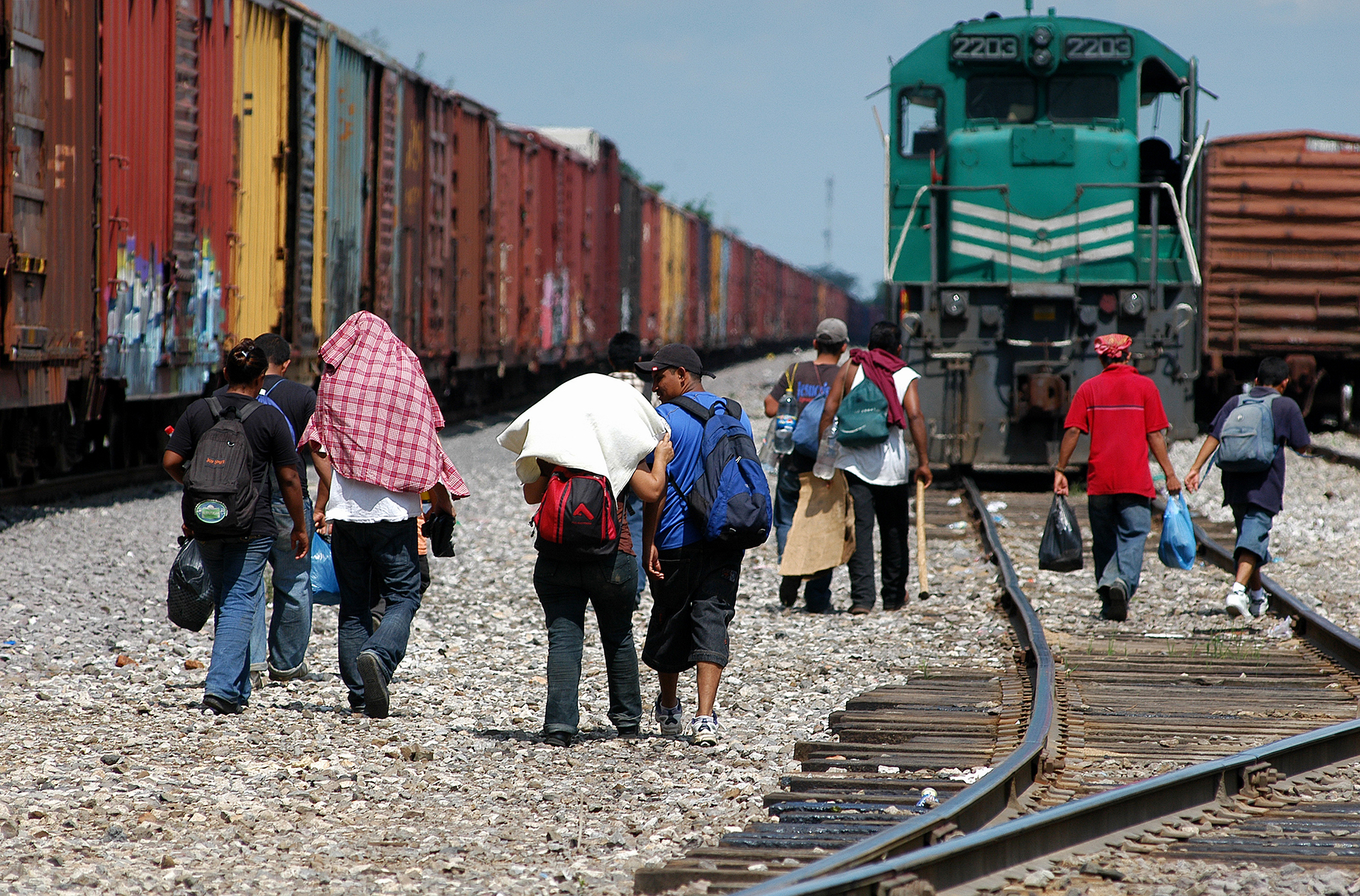 "Central American migrants walk over the tracks to catch the train north, Tierra Blanca, Veracruz, Mexico, 28 June 2009.  Junio 28, 2009. Líneas férreas de Tierra Blanca, Veracruz, México. Migrantes centroamericanos en espera de la salida del tren hacia el norte. Migrants make their way toward Mexico's northern border by foot, bus and most commonly on the top of a network of freight trains. Here migrants in Tierra Blanca, Veracruz state, board ""La Bestia"" (The Beast) also known as ""El tren de la muerte"" (The Death Train)."