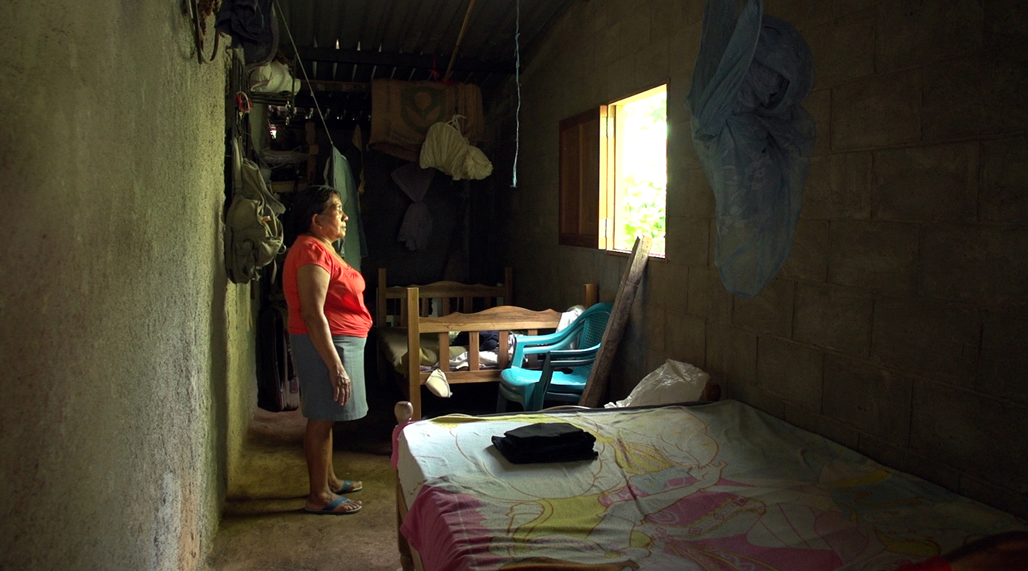 """Marìa Sánchez mother of Teodora Vásquez stands in her daughter's room. Teodora is one of Las 17 group of women sentenced for aggravated himicide out of suspicion of having had an abortion. In 2008, Teodora del Carmen Vásquez was sentenced to 30 years in prison for """"aggravated homicide"""" after suffering a still-birth at work. Teodora, mother of an 11-year-old boy, was expecting a new baby when she started experiencing increasingly severe pain. She called the emergency services but her waters broke soon afterwards. She went into labour, and was unconscious when she gave birth. When she came round, bleeding profusely, her baby was dead. Police at the scene handcuffed her and arrested her on suspicion of murder. Only then did they take her to hospital where she could get the urgent treatment she needed. In El Salvador, women who miscarry or suffer a still-birth during pregnancy are routinely suspected of having had an """"abortion"""". Abortion under any circumstance is a crime, even in cases of rape, incest, or where a woman's life is at risk. This makes women afraid to seek help with pregnancy-related problems, leading inevitably to more preventable deaths."""