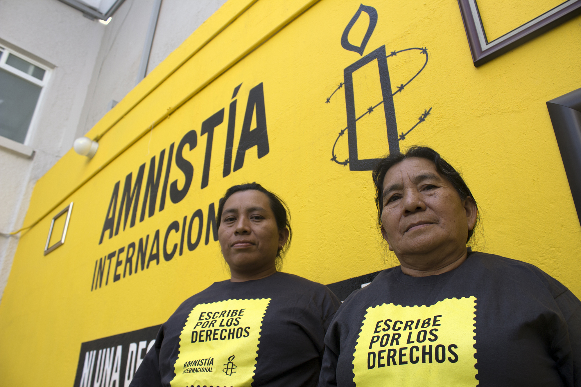 """Cecilia Vásquez Sánchez and María Elena Sánchez, Teodora Vásquez Sánchez's sister and mother, pose at Amnesty International's office in Mexico City. Both are wearing Amnesty International tee shirts. In 2008, Teodora del Carmen Vásquez was sentenced to 30 years in prison for """"aggravated homicide"""" after suffering a still-birth at work. Teodora, mother of an 11-year-old boy, was expecting a new baby when she started experiencing increasingly severe pain. She called the emergency services but her waters broke soon afterwards. She went into labour, and was unconscious when she gave birth. When she came round, bleeding profusely, her baby was dead. Police at the scene handcuffed her and arrested her on suspicion of murder. Only then did they take her to hospital where she could get the urgent treatment she needed. In El Salvador, women who miscarry or suffer a still-birth during pregnancy are routinely suspected of having had an """"abortion"""". Abortion under any circumstance is a crime, even in cases of rape, incest, or where a woman's life is at risk. This makes women afraid to seek help with pregnancy-related problems, leading inevitably to more preventable deaths."""