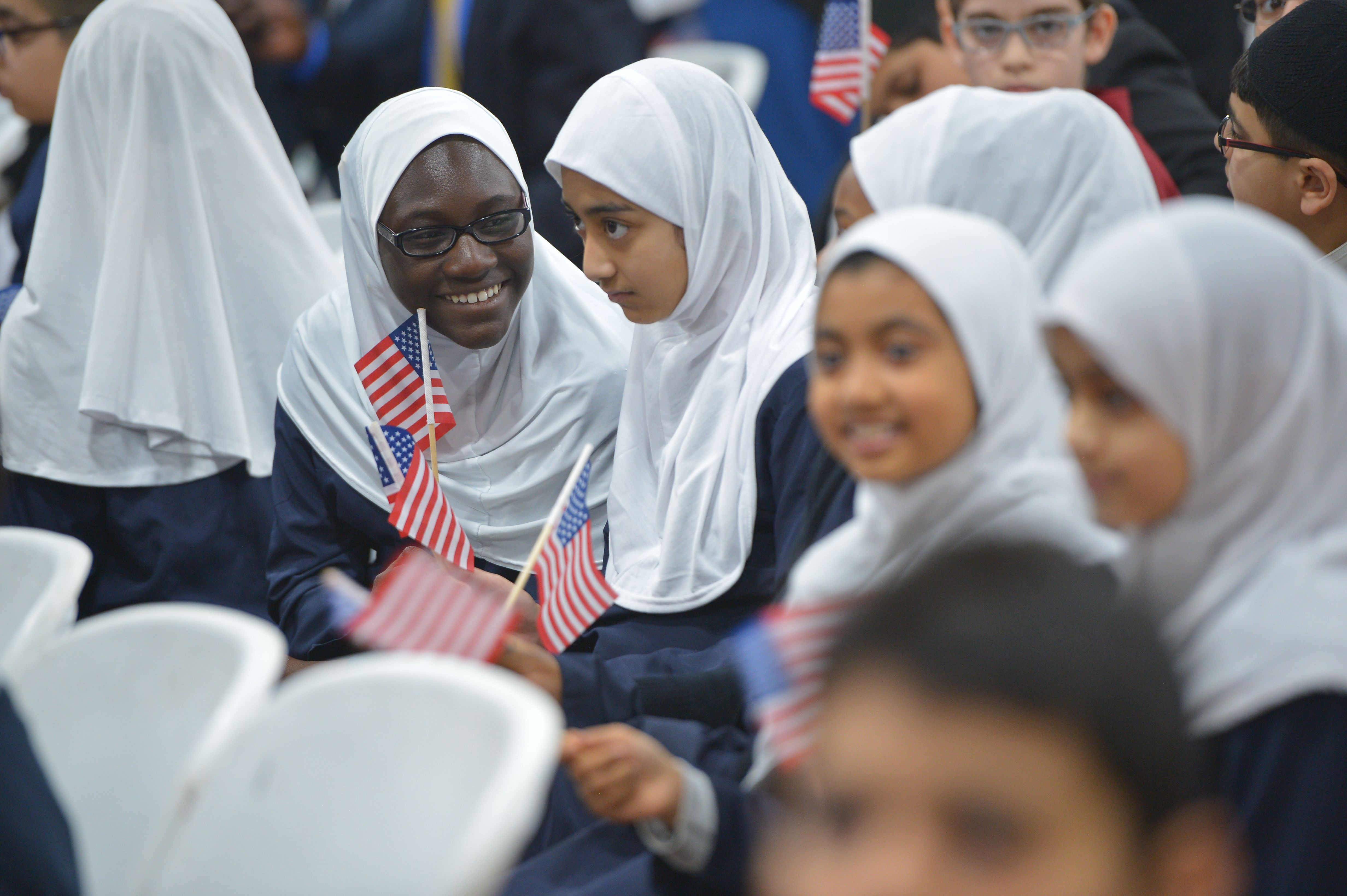Girls hold US flags while waiting for US President Barack Obama after he spoke at the Islamic Society of Baltimore, in Windsor Mill, Maryland on February 3, 2016. / AFP / Mandel Ngan        (Photo credit should read MANDEL NGAN/AFP/Getty Images)