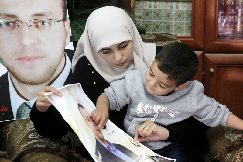 Fayha Shalash, the wife of Palestinian journalist Muhammed al-Qiq, sits with her son at her home in the West Bank village of Dura on January 20, 2016. Al Qiq is seen in the poster.  Photo: Wisam Hashlamoun/APA images
